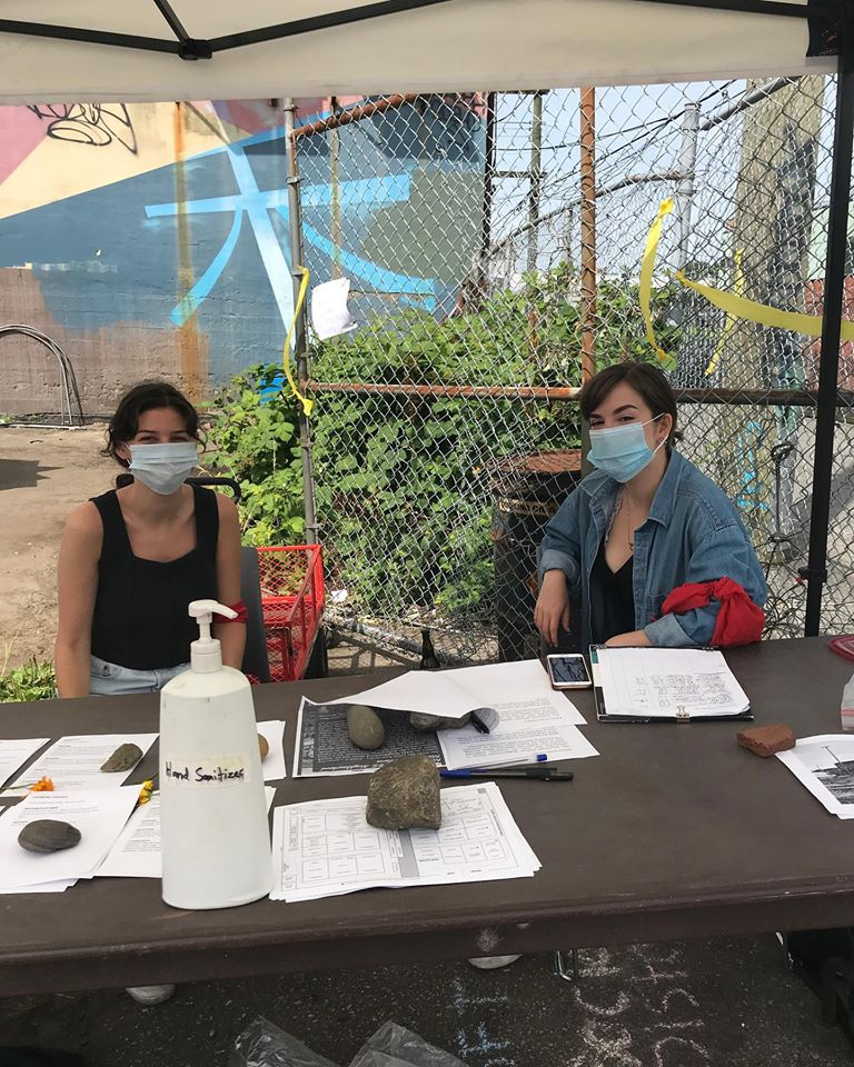 An image of two people wearing safety masks at the welcome table for a mobile market