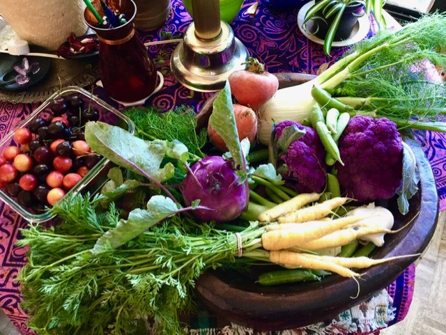An image of brightly coloured garden veggies on a neighbour's dining room table
