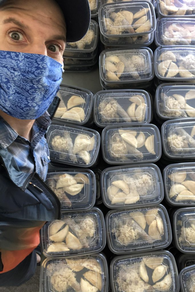 A selfie of Blain, wearing a mask next to many prepared meals