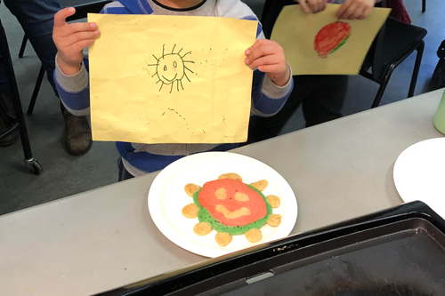 An image of children holding up drawings of the sun, at a table with colourful sun-shaped pancakes