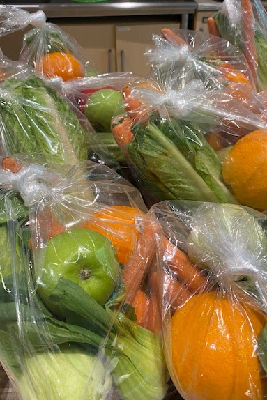 An image of bags of fruits and vegetables, ready for delivery