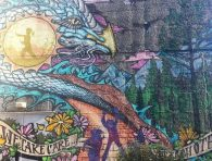 """An image of the mural at Strathcona Community Centre with a painted banner reading: """"We take care of the earth"""""""